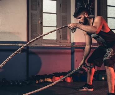 Athlete exercising with battle ropes at a gym