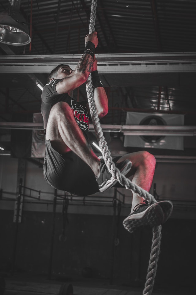 Photo of athlete performing rope climbs in the gym.