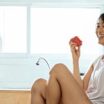 Woman smiling while eating an apple.