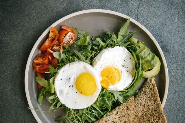 Breakfast with eggs, greens, and toast.