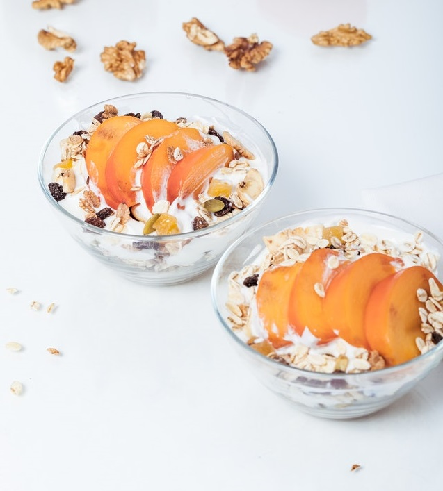 Two bowls of yogurt parfait made with granola and peaches.